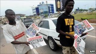 Newspapers sellers on the road trying to sell papers to passing drivers