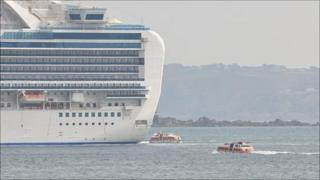 Cruise ship liberty boats travel to and from the Crown Princess anchored off Guernsey