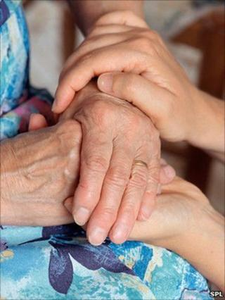 home help carer holding hands with a patient