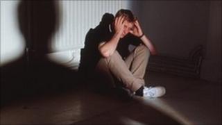 Man cowering in the corner of a dark room