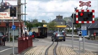 Car following a train across a level crossing at Porthmadog