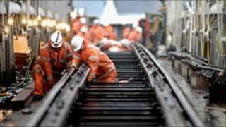 Rail workers laying track