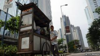 A food vendor pushes his cart at Jakarta