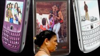 Mumbai woman walks past billboard for mobile phones