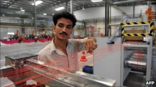 A factory employee checks a monofilament fibre making machine