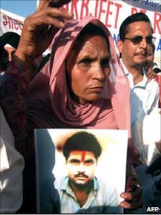 Sarabjit Singh's wife Sukhpreet Kaur holds a photograph of her husband