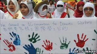 Domestic workers holding a banner demanding more rights
