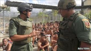 A National Guard general, Antonio Benavidez (left), near sitting inmates in the El Rodeo jail (17 June 2011)