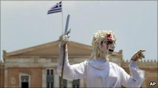 Backdropped by the Greek parliament, theatrical performers hold up a giant marionette representing Justice with a bloodied face