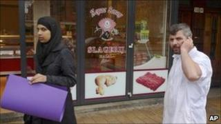 A butcher talks on his mobile phone outside a halal butchers in Amsterdam (31 March 2011)