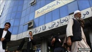 Afghans walk past a branch of the Kabul Bank (file photo)