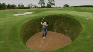 Rory McIlroy in his replica of the infamous Road Hole Bunker at St Andrews
