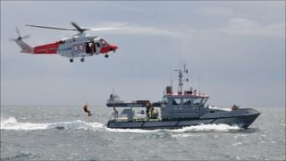 Guernsey firefighter being transferred between the Portland coastguard helicopter and the Sea Fisheries vessel the Leopardess