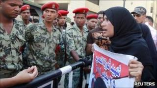 A protester talks to military police in front of the court complex in Suez (6 July 2011)