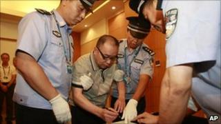 Lai Changxing signs a warrant issued for his arrest at Beijing airport on 23 July 2011