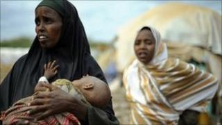 A displaced Somali refugee cradles her severely emaciated child at the Dadaab Refugee camp
