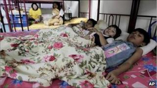 June 8, 2011 photo, Myanmar refugees share a bed in their room in a suburb of Kuala Lumpur, Malaysia