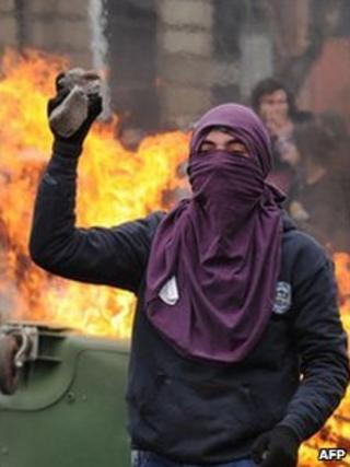 A student throws a stone at riot police officers during a protest against the government of President Sebastian Pinera and a new education law in Santiago, Chile on August 4, 2011.