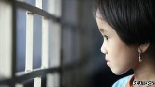 """Burmese refugee Mang Thai Par, 7, looks out of a window at her family""""s flat which they share with three other relatives in Kuala Lumpur June 24, 2011"""