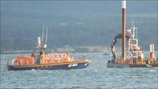 The all-weather lifeboat along with the specialist lifting vessel in Poole harbour