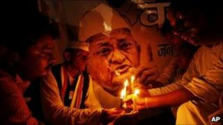 Supporters of Indian anti-corruption activist Anna Hazare hold a candlelight vigil in front of his picture in Allahabad on 16 August 2011