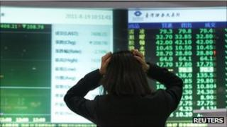 Woman holding her head in front of screens with market prices