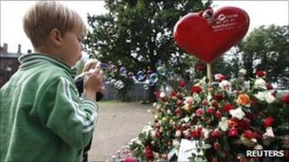 A boy blows bubbles at the Oslo Cathedral as people pay their respects to those killed in last month's bomb and shooting attacks on 21 August 2011