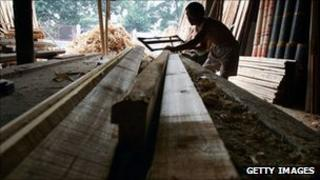 Worker cutting Timber