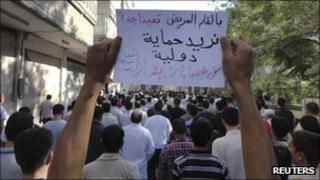 """People protest against President Bashar al-Assad in the city of Suqba, 30 August 2011. The banner reads: """"Need international intervention to protect us from Bashar's gangs"""""""