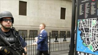 A policeman stands guard on Wall Street with a worker passing by