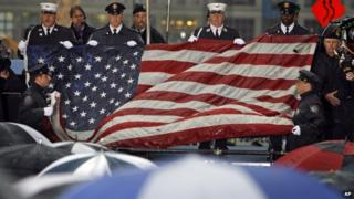 The World Trade Center flag is folded during a memorial service in New York for the victims of the attacks.