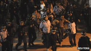 Riot police remove protesters from outside the entrance to the Zhejiang Jinko Solar Co in Haining, Zhejiang province, on 17 September 2011
