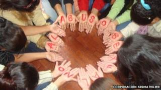 "Women in Colombia form a circle with their hands to form the message ""No to sexual abuse"" during a self-help session in Bogota in March 2011 - photo Corporacion Sisma Mujer"