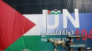Horse cart passes a banner in Hebron supporting the Palestinian UN statehood bid