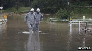 Firemen walk through floods in Toyota, Japan, on 21 September 2011