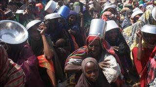 Families from southern Somalia wait for food rations at Maalin refugee camp at Hawlwadag district in Mogadishu on 15 September 2011