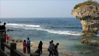Tourists by coastal rock formation