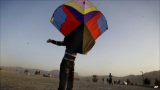 An Afghan boy, named Shams, throws up a kite on the Nader Khan hilltop in Kabul, Afghanistan, Friday 30 September 2011