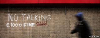 Youth walks past grafitti
