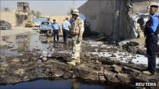A soldier and policemen inspect the site of a bomb attack at a police station in Baghdad's Hurriya district on Wednesday