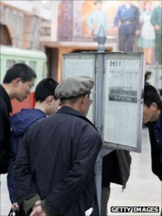 North Koreans read newspaper in metro station