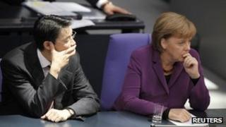 German Chancellor Angela Merkel (right) and Economy Minister Philipp Roesler attend a session of the German parliament in Berlin, 21 October
