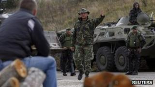 A NATO Kosovo Force (KFOR) soldier gestures towards a Kosovo Serb man in the village of Zupce