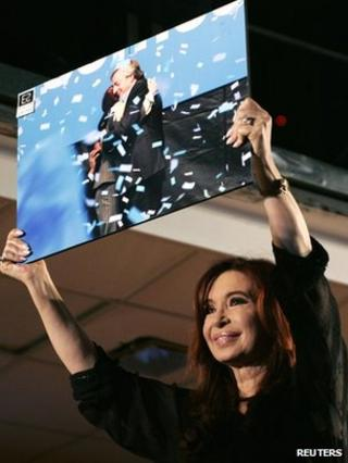 Cristina Fernandez de Kirchner holds up a photo of herself and her late husband Nestor at her victory rally in Buenos Aires on 23 October 2011