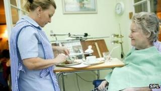 Generic image of a carer cutting up an elderly woman's food