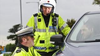 Traffic police officers speak to a driver