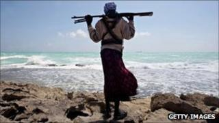 A Somali pirate looks out to sea