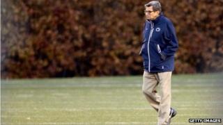 Joe Paterno walks across a field