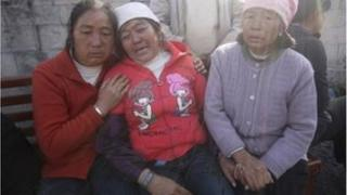 Relatives of trapped coal miners cry outside a coal mine after a gas leakage accident in Shizong county, Yunnan province November 10