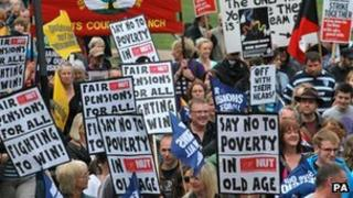 Protesters hold placards in Nottingham city centre during a one day national strike against pension changes and funding cuts to the public sector, June 2011.